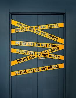 Miejsce zbrodni zamknięte drzwi z żółtymi paskami tekst linia policyjna nie krzyżuje się