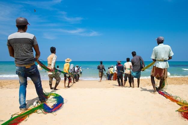 Miejscowi rybacy wyciągają sieci rybackie z oceanu indyjskiego w kosgoda na sri lance. wędkarstwo na sri lance to sposób, w jaki zarabiają na życie.