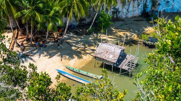 Miejscowi wybierają nową lokalizację, bamboo hut and boats on beach w czasie odpływu, kabui bay w pobliżu waigeo. west papuan, raja ampat, indonezja