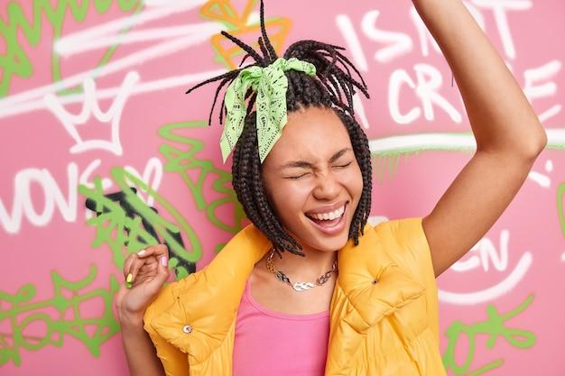 Miejska dziewczyna nosi kamizelkę i tańczy na tle narysowanej ściany graffiti.