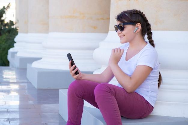 Miejska stylowa nastolatka siedzi obok kolumny, prowadzi wideorozmowy przez telefony komórkowe, używa rąk, rozmawia z przyjaciółmi