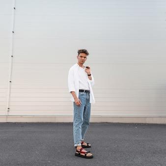 Miejski amerykański młody mężczyzna w stylowych białych i dżinsowych ubraniach w modnych sandałach z czarną płócienną torbą spaceruje na zewnątrz