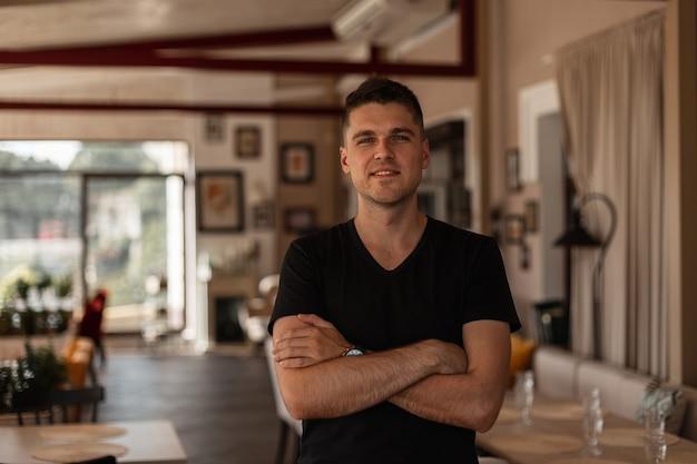 Miejski europejski młody człowiek z modną fryzurą w stylowej czarnej koszulce stoi i uśmiecha się w kawiarni vintage