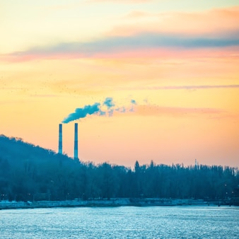 Miejski krajobraz z rurami przemysłowymi i ciężkim dymem. palenie roślin, problem z zanieczyszczeniem powietrza