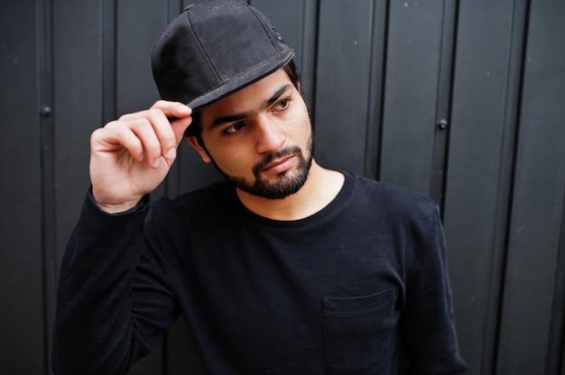Miejski młody hipster indianin nosić wszystko w kolorze czarnym. fajny południowoazjatycki facet w pełnej czapce.