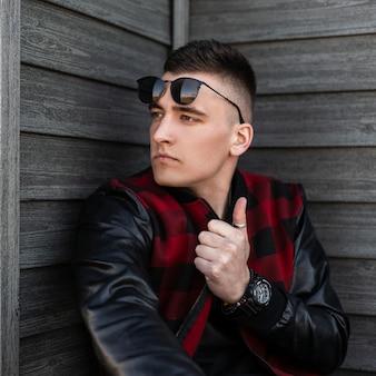 Miejski młody hipster mężczyzna w czarnych okularach przeciwsłonecznych w modnej czerwonej kraciastej kurtce ze skórzanymi rękawami z modną fryzurą pozuje przy drewnianej ścianie w letni dzień