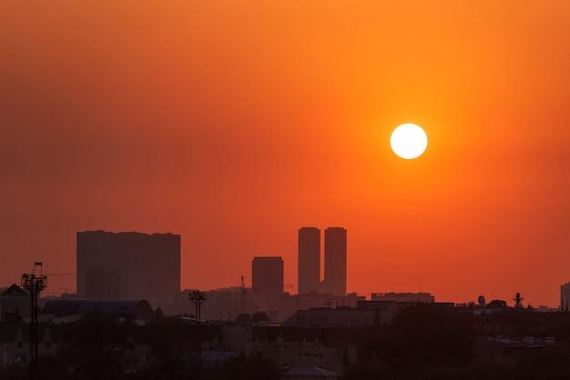 Miejski panoramę podczas pomarańczowego zachodu słońca. gród i okrągłe słońce, zachód słońca latem.