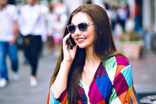 Miejski portret ładnej brunetki kobiety za pomocą smartfona, mówiąc i uśmiechnięty, jasne ubrania, kolory vintage filmu.