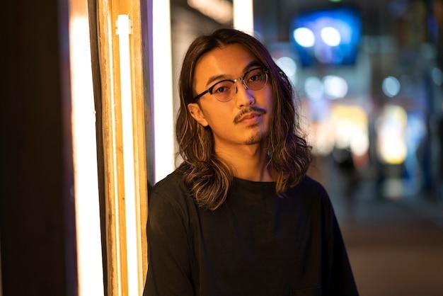 Miejski portret młodego mężczyzny z długimi włosami