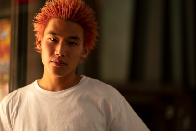 Miejski portret młodego mężczyzny z pomarańczowymi włosami