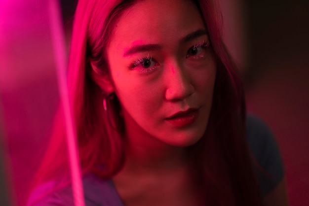 Miejski portret młodej kobiety z długimi różowymi włosami