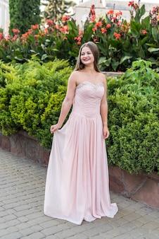 Miejski portret młodej, szczupłej, pięknej modelki w różowej sukience