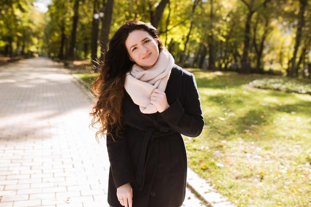 Miejski portret uśmiechniętej brunetki z długimi falującymi włosami pozowanie w parku w słoneczny dzień