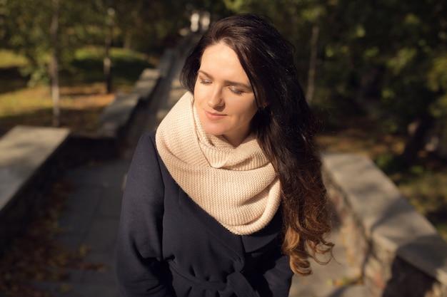 Miejski portret wspaniałej brunetki z długimi falującymi włosami, ubranej w różowy szalik z dzianiny i niebieski płaszcz