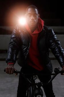 Miejski rowerzysta siedzi na rowerze w nocy