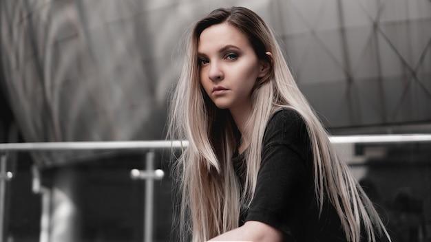 Miejski styl blondynka o surowym wyglądzie stojąca na tle nowoczesnego budynku. ubrana w czarną koszulę. girl power i koncepcja subkultury.