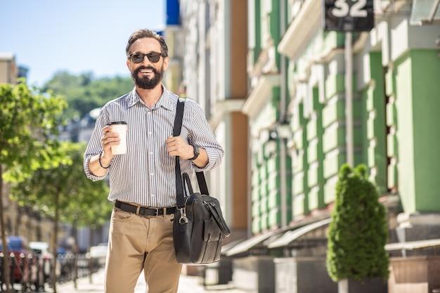 Miejski styl życia. wesoły przystojny mężczyzna pije kawę stojąc na ulicy