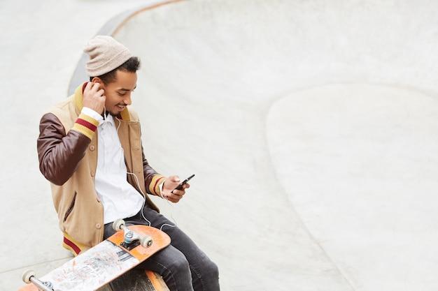 Miejski stylowy hipster facet siedzi obok swojej deskorolki, nosi modne ciuchy,