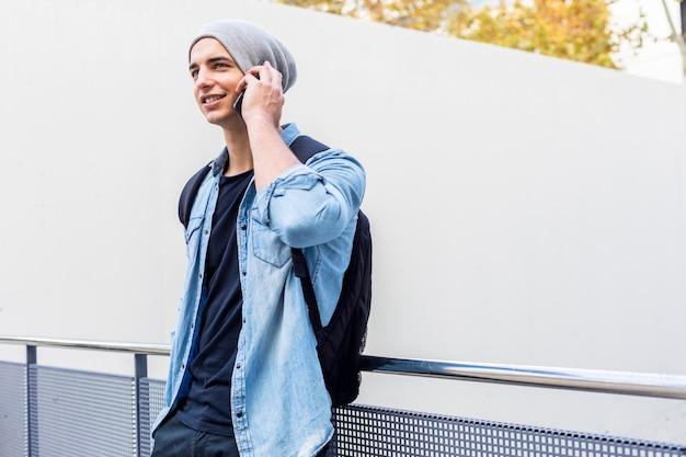Miejski stylowy młody człowiek stojący przy ścianie przy użyciu telefonu komórkowego