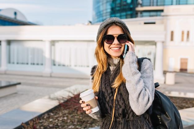 Miejski stylowy portret niesamowitej radosnej młodej kobiety w ciepłym wełnianym swetrze, dzianinowej czapce, nowoczesnych okularach przeciwsłonecznych spacerującej po słonecznym centrum miasta z kawą na wynos. wesołe emocje, miejsce na tekst.