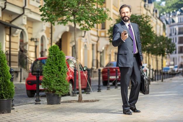 Miejski wygląd zewnętrzny. pełnometrażowy pozytywny biznesmen trzymający smartfona stojąc na ulicy