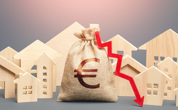 Miejskie budynki mieszkalne i worek pieniędzy euro z czerwoną strzałką w dół