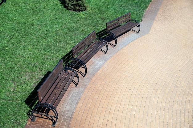 Miejskie kolorowe płytki chodnikowe i drewniane siedzenia z metalowymi balustradami w architekturze krajobrazu