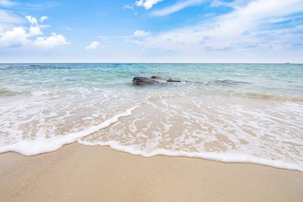 Miękka fala oceanu na piaszczystej plaży z błękitnym niebem.