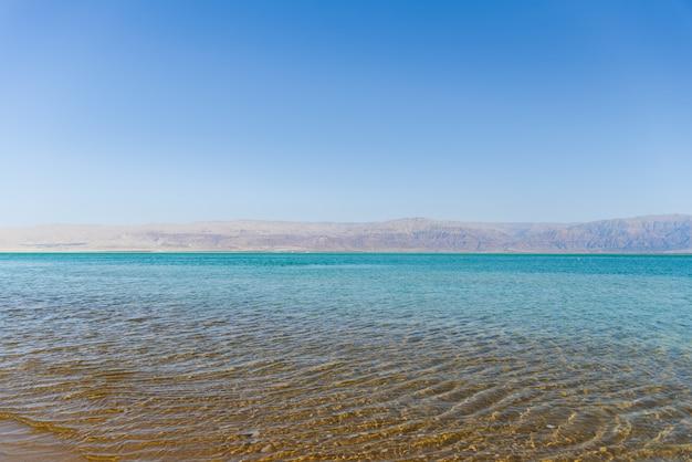 Miękka, krystalicznie czysta woda w morzu w słoneczny dzień z górami na tle. wybrzeże morza martwego.