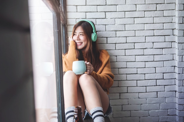 Miękka ostrość młoda kobieta relaksuje z muzyką od hełmofonu w wygodnym domu