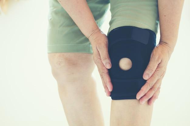 Miękka ostrość stare azjatyckie kobiety uraz kolana na białym tle