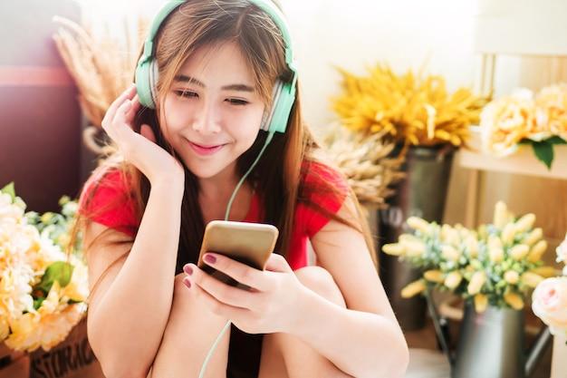 Miękka ostrość szczęśliwa młoda kobieta słuchająca muzyka od mądrze telefonu w wygodnym domu