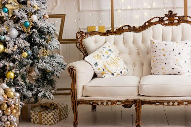 Miękka, przytulna sofa z białymi poduszkami świątecznymi obok udekorowanej choinki w pokoju