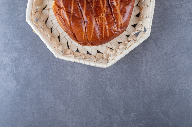 Miękka słodka bułka w wiklinowym koszu na marmurowym stole.