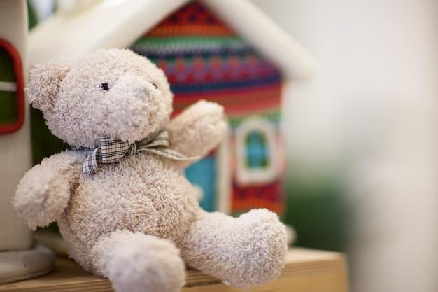 Miękki biały miś na półce w tle mały domek