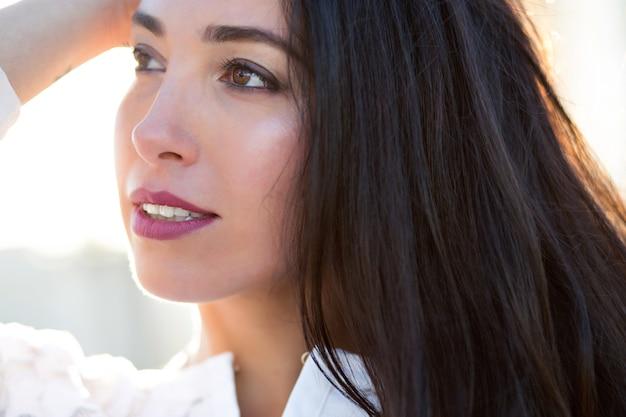 Miękki glam bliska portret pięknej brunetki, doskonałej skóry, długich ciemnych włosów, wieczornego światła słonecznego, eleganckiej glamour pani w średnim wieku.