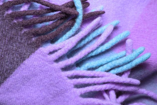 Miękki i ciepły kocyk z wełny alpaki z frędzlami. fioletowy kratę tekstury wełny makro. wełniana krata z frędzlami. koc wełniany