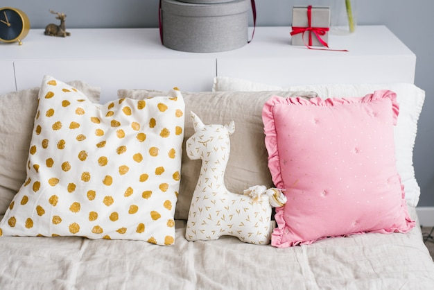 Miękki jednorożec na łóżku z poduszkami