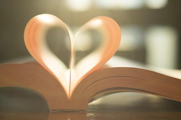 Miękki kształt serca z strony książki papierowej. ciepły, zabytkowy kolor światła słonecznego