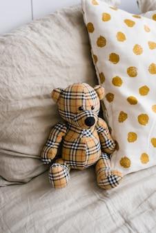 Miękki pluszowy miś wykonany z kraciastej tkaniny w otoczeniu poduszek