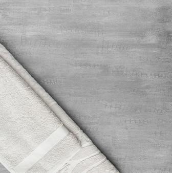 Miękki ręcznik w szarym ozdobnym tle stiukowym. widok z góry, na białym tle