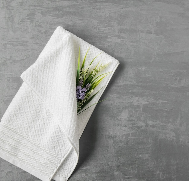 Miękki ręcznik z kwiatkiem w szarym ozdobnym tle stiuku. widok z góry, na białym tle