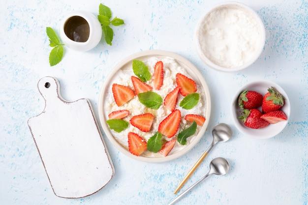 Miękki ser śmietankowy lub organiczny twaróg ze świeżymi truskawkami i liśćmi mięty na jasnoniebieskim tle