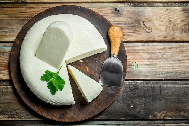 Miękki ser z liśćmi mięty. na drewnianym tle.