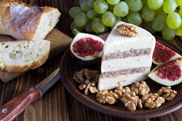 Miękki ser z orzechami, owocami i pieczywem na drewnie