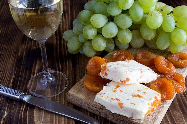 Miękki ser z suszonymi morelami, lampką wina i owocami na drewnianym tle