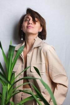 Miękki, wewnętrzny portret kaukaskiej delikatnej kobiety w beżowym garniturze bez stanika, pozująca za palmą tropikalną rośliną, szary.