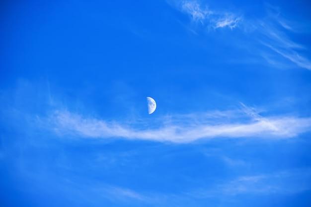 Miękkie chmury i księżyc spotkały się na jasnym niebieskim niebie. naturalne piękno