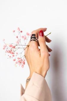 Miękkie, delikatne zdjęcie dłoni kobiety z dużym pierścieniem czerwony manicure trzyma słodkie małe różowe suszone kwiaty na białym tle.