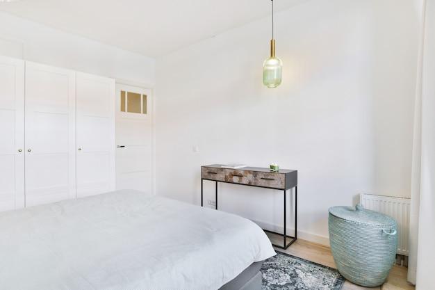 Miękkie łóżko w sypialni z białym wnętrzem w minimalistycznym stylu w mieszkaniu